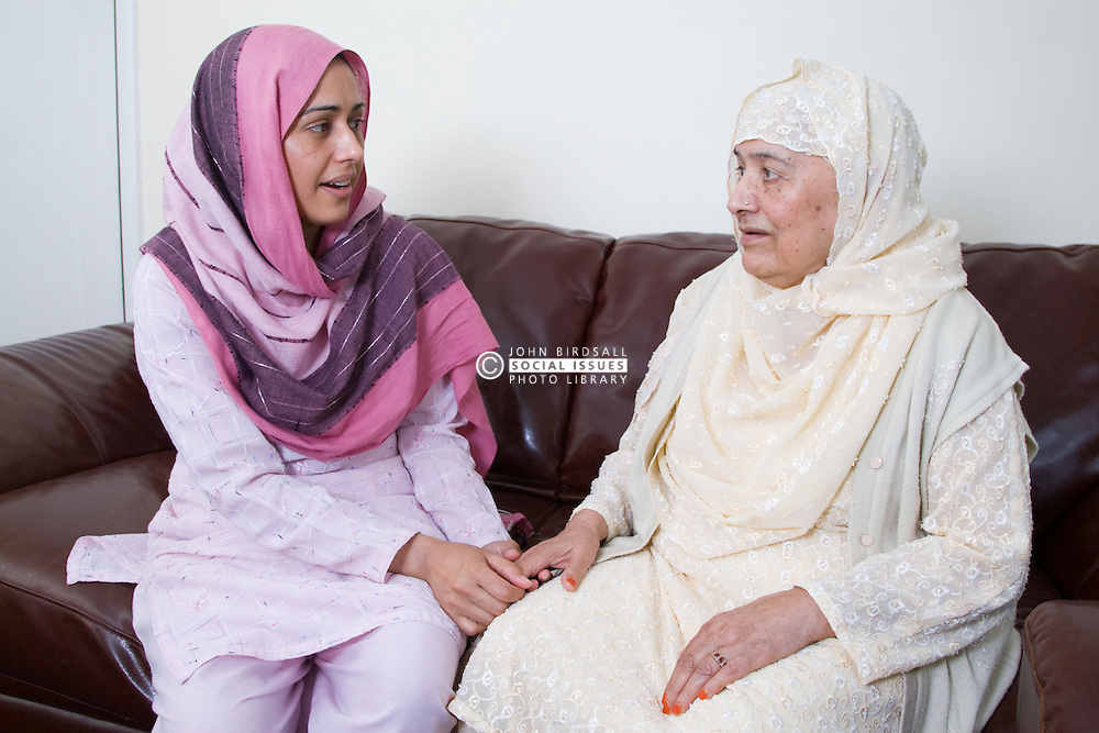 Young female carer and older woman talking together,