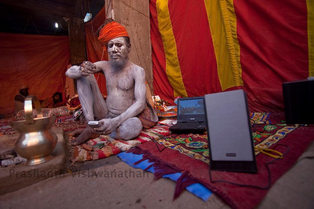 A naked Naga sadhu texts on his phone as his dvd player plays spiritual songs on portable speakers during the Maha Kumbh ceremony in Haridwar, February 11, 2010.  Photographer:Prashanth Vishwanathan