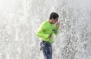 BEA AHBECK/NEWS-SENTINEL<br /> City of Lodi's Water and waste water department's Johnny Morales emerges from the water as he works to turn off the water spewing from a fire hydrant after a car backed into it in a parking lot near the intersection of Ham and Kettleman in Lodi Wednesday, Jan. 13, 2016. City workers estimated it took about 20 minutes to shut the water line off, and most of the parking lot was covered in inches-deep water.