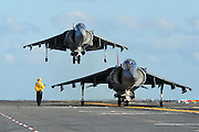 AN AV-8B Harrier awaits to take off while another Harrier comes in for landing on the flight deck of USS Makin Island. Photo by John Lill