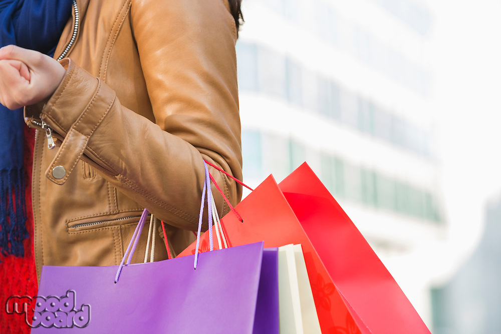 Mid section of woman carrying shopping bags