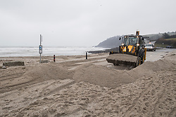 © Licensed to London News Pictures. 02/03/2018. FALMOUTH CORNWALL, UK. Clearing the blocked roads. Storm Emma caused damage to the beaches and businesses of Falmouth at the morning high spring tide today. The strong wind and the spring tide caused a beach to be washed away at Gylly beach. At Swanpool beach the beach was washed onto the road causing it to be blocked .  Photo credit: MARK HEMSWORTH/LNP
