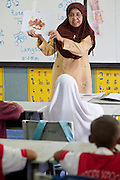"Sept. 27, 2009 -- PATTANI, THAILAND: A Muslim teacher teaches English to students at the Gahong School in Pattani, Thailand, Sept 27. Schools and school teachers have been frequent targets of Muslim insurgents in southern Thailand and the army now provides security at many government schools. Thailand's three southern most provinces; Yala, Pattani and Narathiwat are often called ""restive"" and a decades long Muslim insurgency has gained traction recently. Nearly 4,000 people have been killed since 2004. The three southern provinces are under emergency control and there are more than 60,000 Thai military, police and paramilitary militia forces trying to keep the peace battling insurgents who favor car bombs and assassination.  Photo by Jack Kurtz / ZUMA Press"