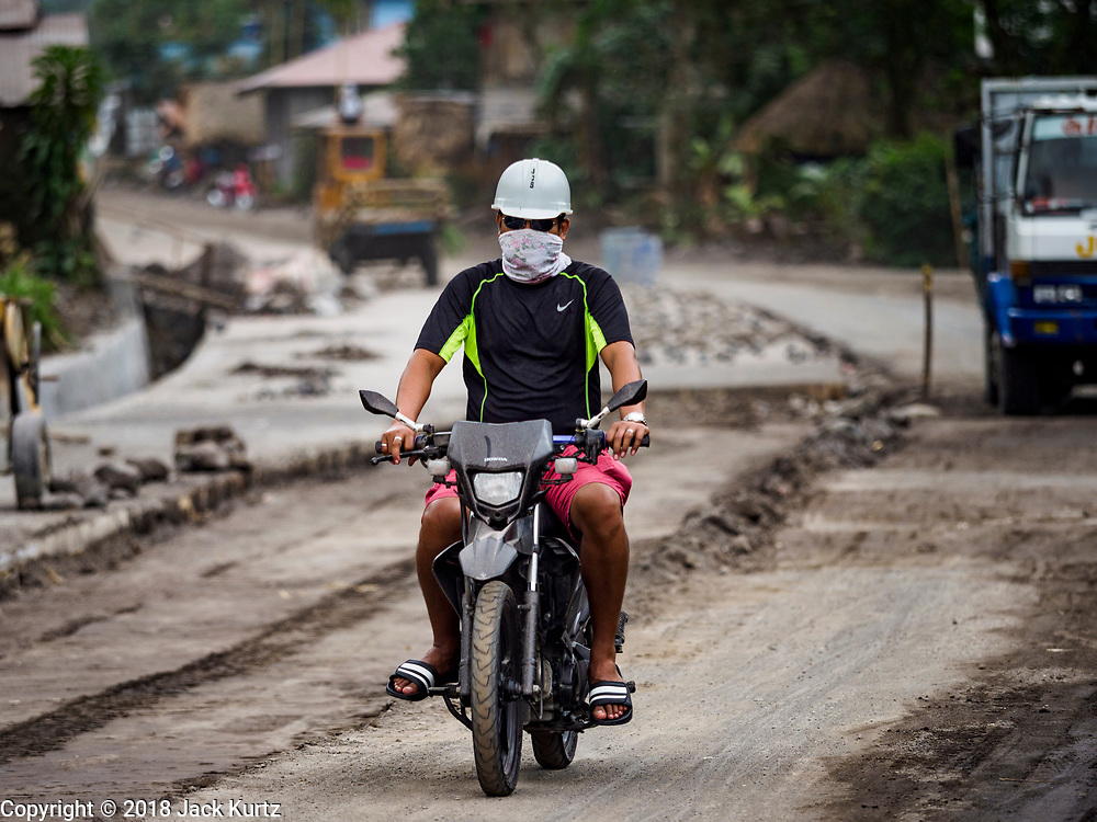 "22 JANUARY 2018 - GUINOBATAN, ALBAY, PHILIPPINES: A man on a motorcycle in Guinobatan wears a face mask while he drives through the community. Several communities in Guinobatan were hit ash falls from the eruptions of the Mayon volcano and many people wore face masks to protect themselves from the ash. There were a series of eruptions on the Mayon volcano near Legazpi Monday. The eruptions started Sunday night and continued through the day. At about midday the volcano sent a plume of ash and smoke towering over Camalig, the largest municipality near the volcano. The Philippine Institute of Volcanology and Seismology (PHIVOLCS) extended the six kilometer danger zone to eight kilometers and raised the alert level from three to four. This is the first time the alert level has been at four since 2009. A level four alert means a ""Hazardous Eruption is Imminent"" and there is ""intense unrest"" in the volcano. The Mayon volcano is the most active volcano in the Philippines. Sunday and Monday's eruptions caused ash falls in several communities but there were no known injuries.    PHOTO BY JACK KURTZ"