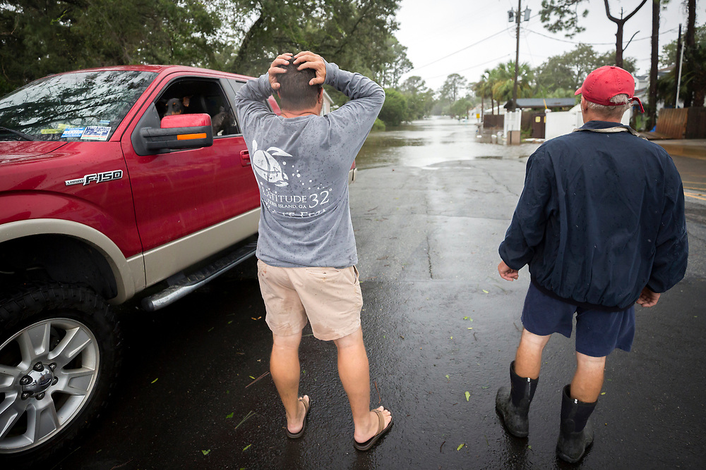 Joey Spalding, center. reacts to looking at the street where he live, Monday, Sept., 11, 2017, on Tybee Island, Ga. Spalding just finished repairing his house from nine inches of water after Hurricane Matthew past the island last year. He said the Tropical Storm Irma brought three feet of storm surge into his living room today.  (AP Photo/Stephen B. Morton)
