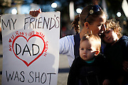 "Susan Shobe (C) sings ""Let There Be Peace on Earth"" with her children Violet Schorr, 1, (L) and Willow Schorr, 3, (R) as she knelt at a memorial outside the hospital where victims of the shootings are recovering in Tucson, Arizona January 10, 2011.  Shobe's best friend's father Ron Barber was shot in the attack. Barber, district director for congresswoman Gabrielle Giffords spent more than six hours in surgery January 8 after being shot twice during the shootings that left six people dead.  REUTERS/Rick Wilking (UNITED STATES)"