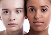 Portrait of two young female friends against white background
