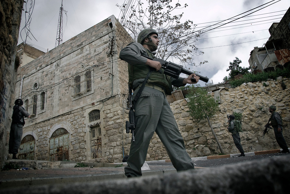 Israeli soldiers take position during clashes in the West Bank city of Hebron, Monday, Feb. 22, 2010. Palestinians clashed with Israeli troops in Hebron amid outrage over Israel's plan to restore two flashpoint Jewish holy sites in the occupied territory.