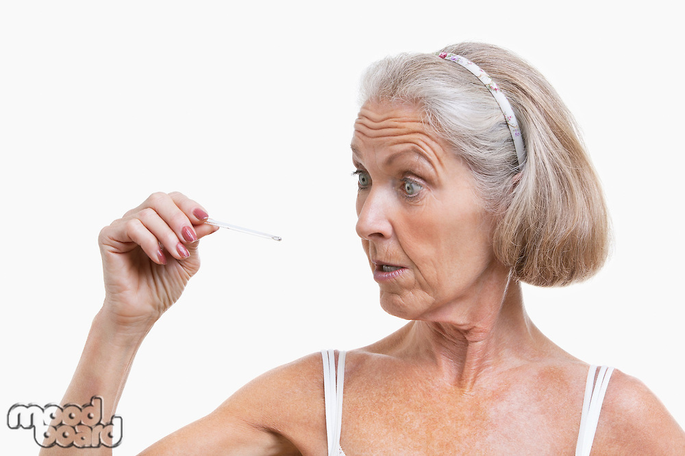 Senior woman checking thermometer against white background