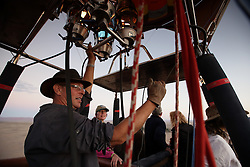 NAMIBIA SOSSUSVLEI 21APR14 - Pilot Eric Hesemans steers his balloon during a flight with Namib Sky Balloon Safaris in Sossusvlei, Namib Desert, Namibia.<br />