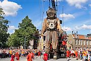 Nederland, Leeuwarden, the Netherlands, 17-8-2018 In het kader van Leeuwarden culturele hoofdstad van europa trokken drie reuzen van het Franse theatergezelschap Royal de Luxe door Leeuwarden, Ljouwert . De duiker is 11 meter hoog, het meisje 5 en de hond 3 . De poppen worden als marionetten bewogen door mensen, lakeien, die aan touwen hangen of trekken . Een muziekgroep op een wagen rijdt erachter . A marionette of French streettheatre Royal de Luxe parades through the streets in the european capital of culture 2018, Leeuwarden. It presents a new story based on the saga of the Giants called Grand patin dans la glace and is one of three giants. The others are the girl and the dog. Foto: Flip Franssen