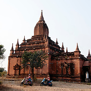 Myanmar (Burma). Bagan. Two French women on  e bikes in front of a temple.