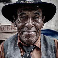 A close up portrait of a Bolivian man resting in his suit and sombrero after playing trumpet for the festivities for the Anniversary of Coroico.