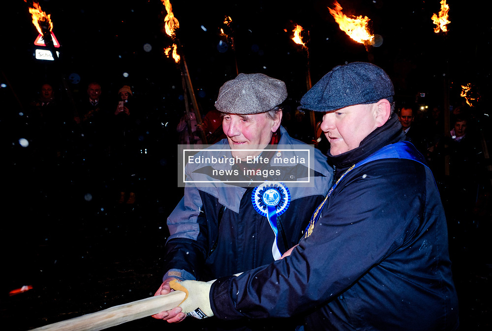 The Biggar Hogmanay bonfire lit at 9.30pm on Hogmanay by local resident John Michie (L) assisted by one of the Biggar Cornets.<br /> <br /> This is probably the biggest new year bonfire anywhere in the UK and continues a tradition going back hundreds of years.<br /> <br /> <br /> (c) Andrew Wilson | Edinburgh Elite media