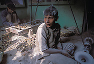 Child factory worker in India tends a polishing wheel.