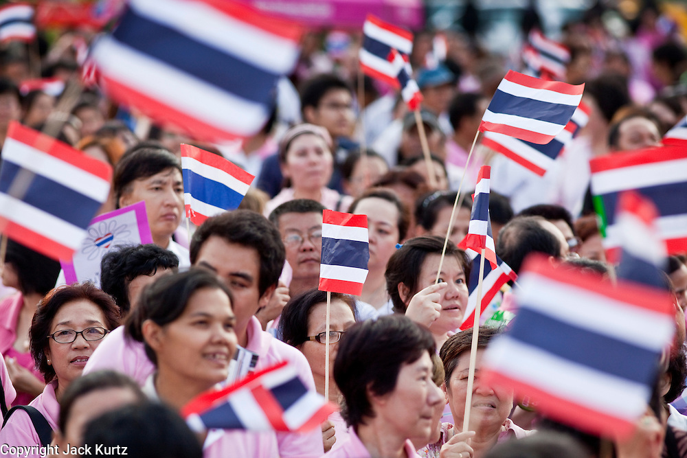 """Apr. 2, 2010 - BANGKOK, THAILAND: Thai protestors clad in pink wave the Thai flag during a peace protest in Bangkok, Friday. Thousands of """"Pink Shirts,"""" who claim to be neither """"Red Shirts"""" nor """"Yellow Shirts"""" nicknames for Thailand's dueling political forces, gathered in Lumpini Park in central Bangkok Friday evening to call for """"peace in the land,"""" a play on the Red Shirts slogan, """"Red in the Land."""" The """"Pink Shirts"""" represented educators, business people and people in the tourist industry, all of which have been hurt by the ongoing political protests that have disrupted life in the Thai capital. The """"Pink Shirts"""" stressed their loyalty to His Majesty Bhumibol Adulyadej, the King of Thailand, and chanted for the Red Shirts to """"Get Out!"""" of Bangkok.    PHOTO BY JACK KURTZ"""