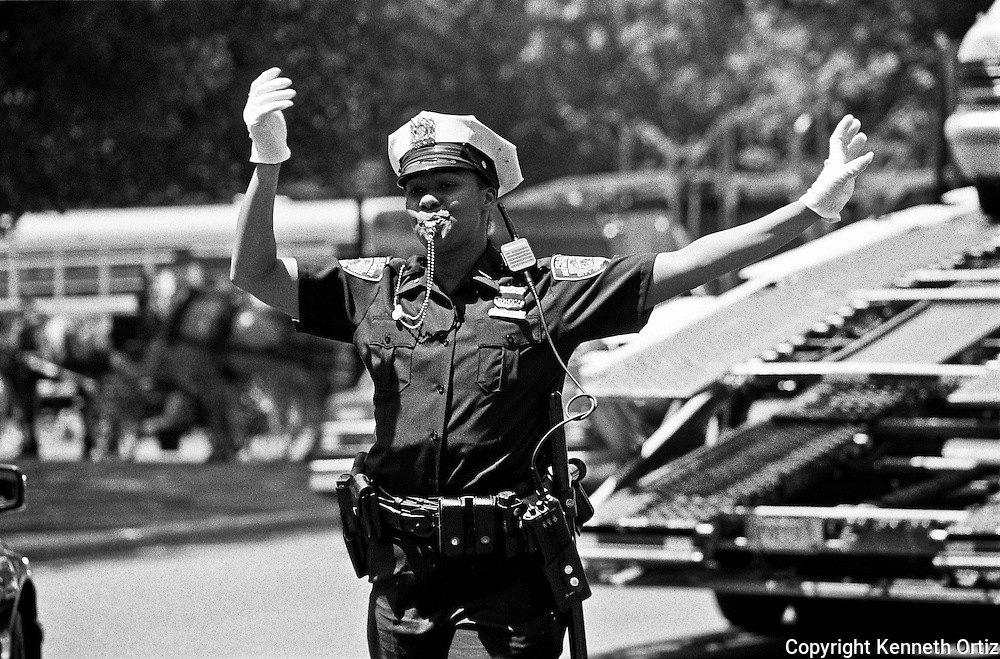 Police woman directing traffic on the corner of 60th Street and 5th Avenue in New York City.