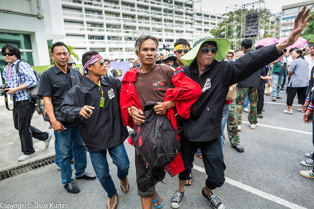 26 NOVEMBER 2013 - BANGKOK, THAILAND: Anti-government protestors detain a man they said was a pro-government Red Shirt during a rally at the Ministry of Finance in Bangkok. The man was paraded through a crowd before being kicked out of the compound and put back on the street. Protestors opposed to the government of Thai Prime Minister Yingluck Shinawatra spread out through Bangkok this week. Protestors have taken over the Ministry of Finance, Ministry of Sports and Tourism, Ministry of the Interior and other smaller ministries. The protestors are demanding the Prime Minister resign, the Prime Minister said she will not step down. This is the worst political turmoil in Thailand since 2010 when 90 civilians were killed in an army crackdown against Red Shirt protestors. The Pheu Thai party, supported by the Red Shirts, won the 2011 election and now govern. The protestors demanding the Prime Minister step down are related to the Yellow Shirt protestors that closed airports in Thailand in 2008.     PHOTO BY JACK KURTZ