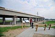 Nederland, Andelst 3-4-2012Wegverbreding van de A50 tussen de knooppunten Ewijk en Valburg. Onderdeel van deze wegverbreding is de bouw van een extra brug over Waal. De laatste brug van deze omvang die Rijkswaterstaat realiseerde, was de Martinus Nijhoffbrug over de Waal bij Zaltbommel in 1995. Mensen bekijken een bord met informatie over de constructie van deze oeververbinding.Foto: Flip Franssen/Hollandse Hoogte