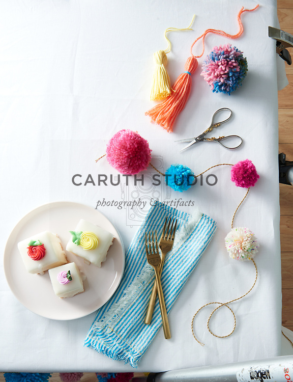 Pom-pom garland and tassels with iced cakes on tabletop