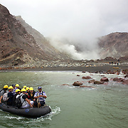 Tourists arrive at White Island leaving a main boat by inflated dingy to explore White Island. .Whakaari or White Island is an active volcano, situated 48 km from the east coast of the North Island of New Zealand, in the Bay of Plenty. .The island is roughly circular, about 2 km in diameter, and rises to a height of 321 m  above sea level. Sulphur mining was attempted but was abandoned in 1914 after ten workers were killed. It is New Zealand's only active marine volcano and perhaps the most accessible on earth, attracting scientists and volcanologists worldwide as well as many tourists. It is part of the Taupo Volcanic Zone.. The main activities on the island now are guided tours and scientific research. White Island, New Zealand,. 5th December 2010.  Photo Tim Clayton.