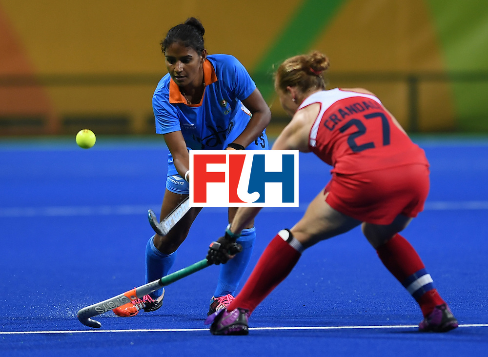 India's Poonam Rani hits the ballas the USA's Lauren Crandall looks on during the women's field hockey USA vs India match of the Rio 2016 Olympics Games at the Olympic Hockey Centre in Rio de Janeiro on August, 11 2016. / AFP / MANAN VATSYAYANA        (Photo credit should read MANAN VATSYAYANA/AFP/Getty Images)