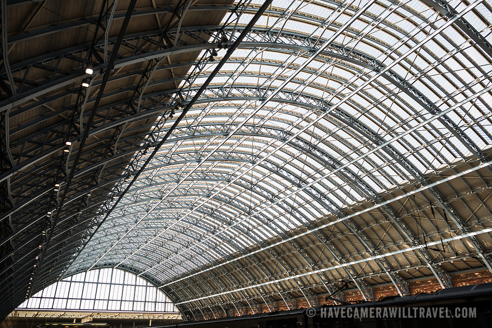Wide shot of the distinctive iron and glass arched cover over the platforms of St Pancras Railway Station (now known as St Pancras International). The renovated station features distinctive Victorian architecture and serves as a Eurostar terminal for high-speed trains to Europe. There are also platforms for domestic train services. The distinctive train shed roof was designed by William Henry Barlow.