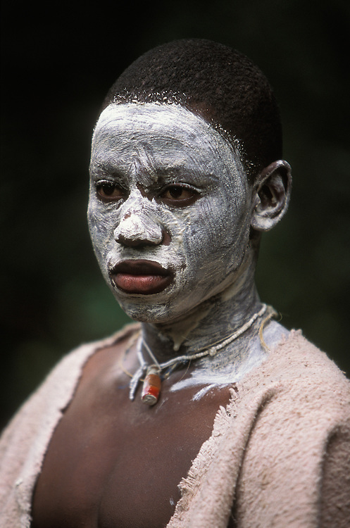 Young Xhosa initiate, who is going through the traditional Xhosa male initiation rite, in Knysna, South Africa, in December 2006. He has been circumcised and is now spending a month in seclusion in a special initiation camp. His face is painted white to ward off attacks by witches and a vial with magic potion around his neck offers extra protection.