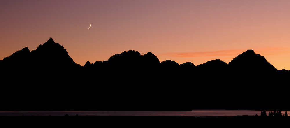 The waxing autumn moon sets over the Grand Tetons and Jackson Lake in Grand Teton National Park.