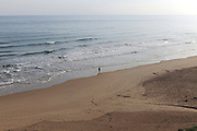 Woman silhouette walking alone along beach shoreline, Bellreguard, near Gandia, Valencia province, Spain