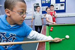 Child learning to play pool at Greenlane Youth Centre; Nottingham,
