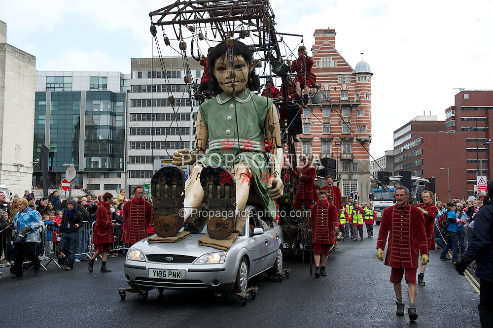 LIVERPOOL, ENGLAND - Sunday, April 22, 2012: The Little Girl Giant gets a lift on top of an old Ford Mondeo as she passes through the streets of Liverpool as part of Sea Odyssey - a Giant Spectacular. Two marionettes controlled by lilliputians, a driver and a girl, his niece, roam through the city's streets looking for each other. The free event, organised by French company Royal de Luxe is one of a series of events marking the 100th anniversary of the sinking of the Titanic. (Pic by David Rawcliffe/Propaganda)