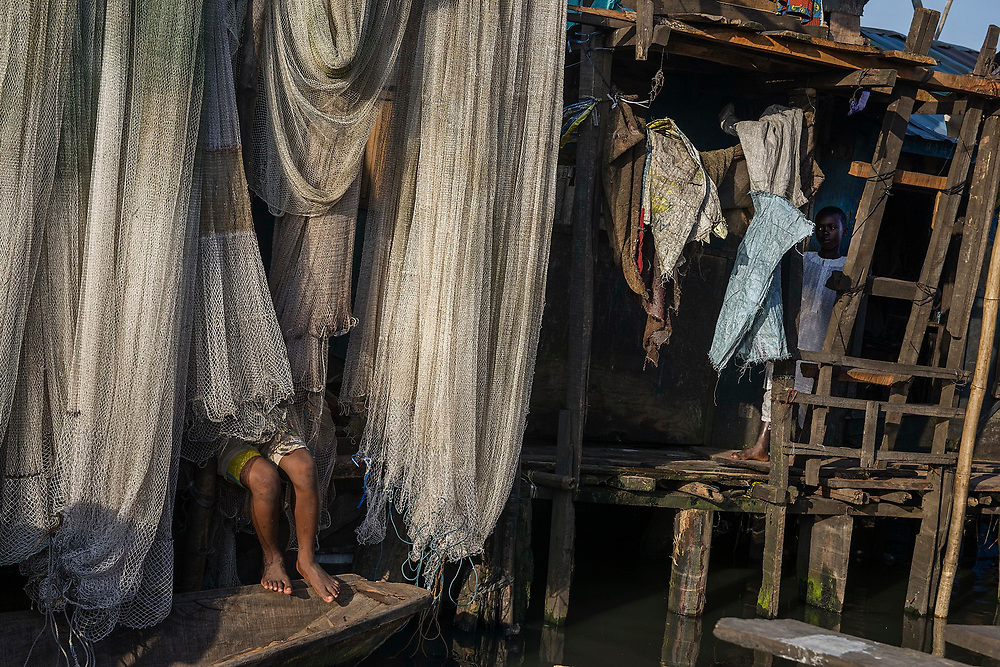 A boy, half hidden by the fishing nets he is repairing, works at the waterside in the Makoko slum.