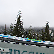 "Winter Olympics, Vancouver, 2010.A Bobsleigh on track during the Bobsleigh Four-man competition  at The Whistler Sliding Centre, Whistler, during the Vancouver Winter Olympics. 25th February 2010. Photo Tim Clayton.'BOB'..Images from the Four-man Bobsleigh Competition. Winter Olympics, Vancouver 2010..History was made at the Whistler Sliding Centre when the USA four-man bobsleigh team, led by Steven Holcomb took the Gold. The first time since 1948, a gap of 62 years, since the USA have won an Olympic Bobsleigh gold and they did it with their sleigh named ""Night Train""...The four days of practice and competition show the tension, nervousness and preparation as the teams of hardened men cope with the challenge of traveling at average speeds of over 150 km an hour. Indeed, five teams had already pulled out of the event before the opening heats because of track complexity, speed and fear, and on the final day, another four teams did not start after six crashes in the first two heats...Teams warm up behind the start complex, warming muscles in the cold in preparation for the explosive start. Many teams prepare in silence, mentally preparing themselves as they wait at the top of the run, in the bobsleigh sheds and the loading areas for their turn. When it's time to slide each team performs it's own starting ritual, followed by the much practiced start out of the blocks for just over four seconds, the teams are then in the hands of the accomplished drivers as they hurtle down the track for just over fifty seconds...Spectators clamber for the best position on track to see the sleighs for a split second, many unsuccessfully try to capture the moments on camera, The rumble of the sleigh is heard then the crowds gasp as it hurtles past in a blur...The American foursome of  Steven Holcomb, Justin Olsen, Steve Mesler and Curtis Tomasevicz finished with a pooled four-heat time of 3min 24.46sec. The German team led by Andre Lange won the Silver Medal in a combined time of 3min 24."