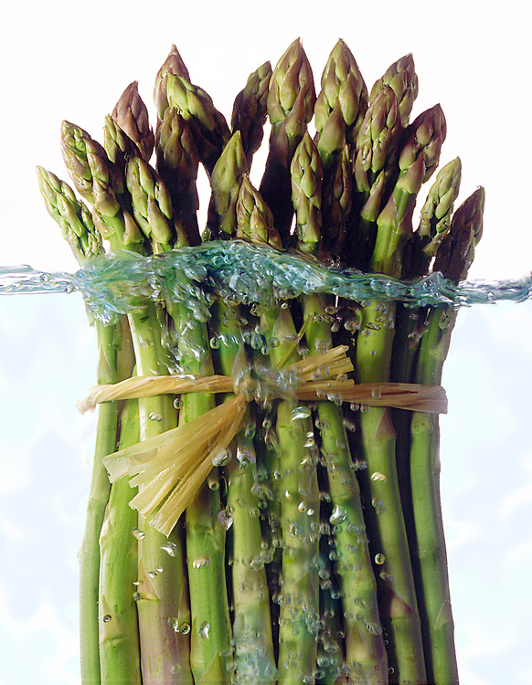asparagus bunch in boiling water see through on a white background