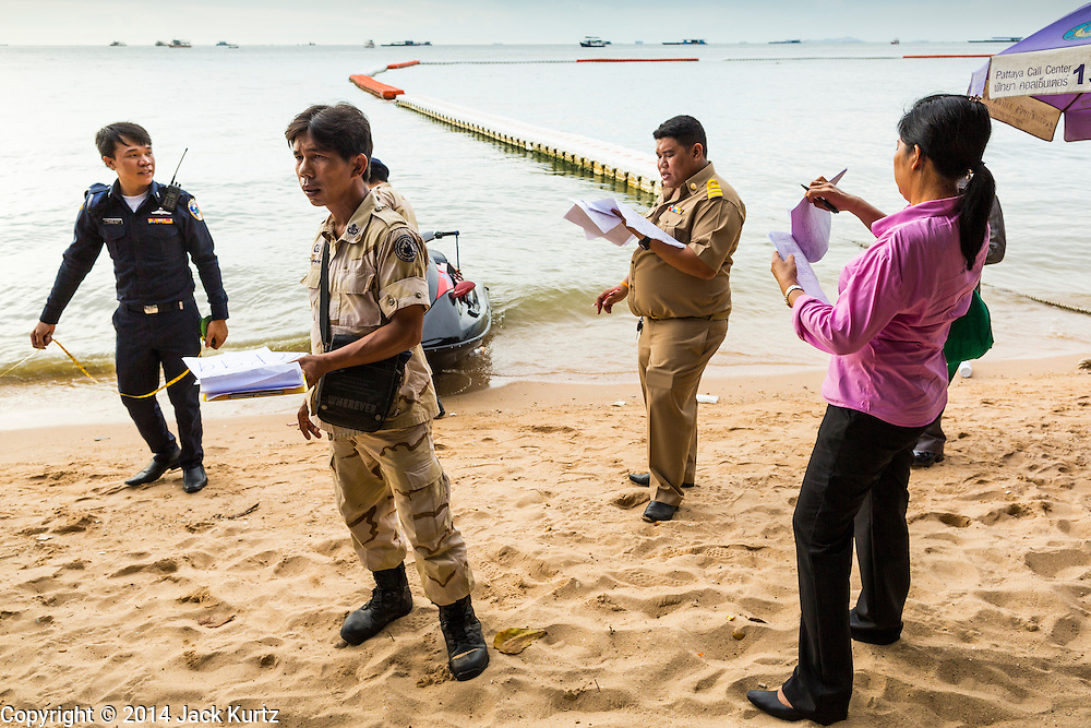 """26 SEPTEMBER 2014 - PATTAYA, CHONBURI, THAILAND:  Pattaya city officials and police walk Pattaya Beach checking on unlicensed businesses on the beach. Pataya, a beach resort about two hours from Bangkok, has wrestled with a reputation of having a high crime rate and being a haven for sex tourism. After the coup in May, the military government cracked down on other Thai beach resorts, notably Phuket and Hua Hin, putting military officers in charge of law enforcement and cleaning up unlicensed businesses that encroached on beaches. Pattaya city officials have launched their own crackdown and clean up in order to prevent a military crackdown. City officials have vowed to remake Pattaya as a """"family friendly"""" destination. City police and tourist police now patrol """"Walking Street,"""" Pattaya's notorious red light district, and officials are cracking down on unlicensed businesses on the beach.    PHOTO BY JACK KURTZ"""