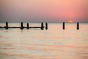 Israel, Beit Yanai, Poles in the sea the remains of a wharf at sunset