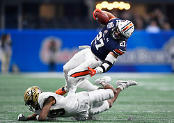 Auburn Tigers fullback Chandler Cox (27) is flipped up by UCF Knights defensive back Mike Hughes (19) during the second half of the Chick-fil-A Peach Bowl NCAA college football game at the Mercedes-Benz Stadium in Atlanta, January 1, 2018. UCF won 34-27 to go undefeated for the season. (David Tulis via Abell Images for Chick-fil-A Peach Bowl)