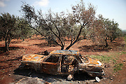 A Mercedes Taxi was set on fire in an olive orchard by Assad loyal forces during an attack on Ain Sauda in April, Idlib Province, Syria.