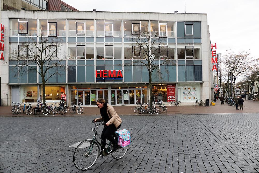 Een fietser rijdt over de Grote Markt langs de vestiging van de Hema in het centrum van Nijmegen.