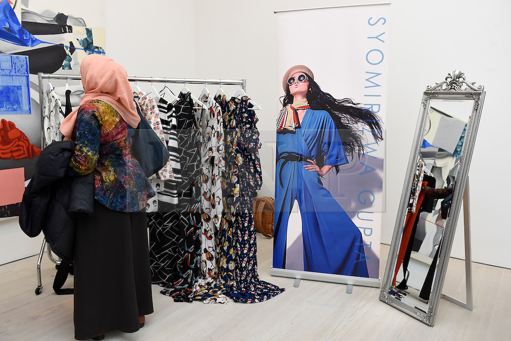 © Licensed to London News Pictures. 18/02/2017. London, UK.  A visitor browses garments at the UK's first London Modest Fashion Week taking place this weekend at the Saatchi Gallery.  The two day event sees 40 brands from across the world come together to showcase their collections for Muslim and other religious women. Photo credit : Stephen Chung/LNP