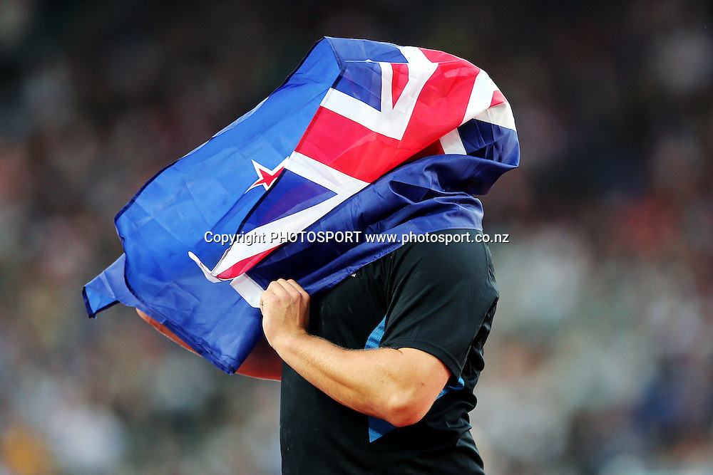 Tom Walsh of New Zealand tries to hold up a New Zealand flag properly after winning silver in the Mens Shot Put final. Glasgow 2014 Commonwealth Games. Athletics, Hampden Park, Glasgow, Scotland. Monday 28 July 2014. Photo: Anthony Au-Yeung / photosport.co.nz