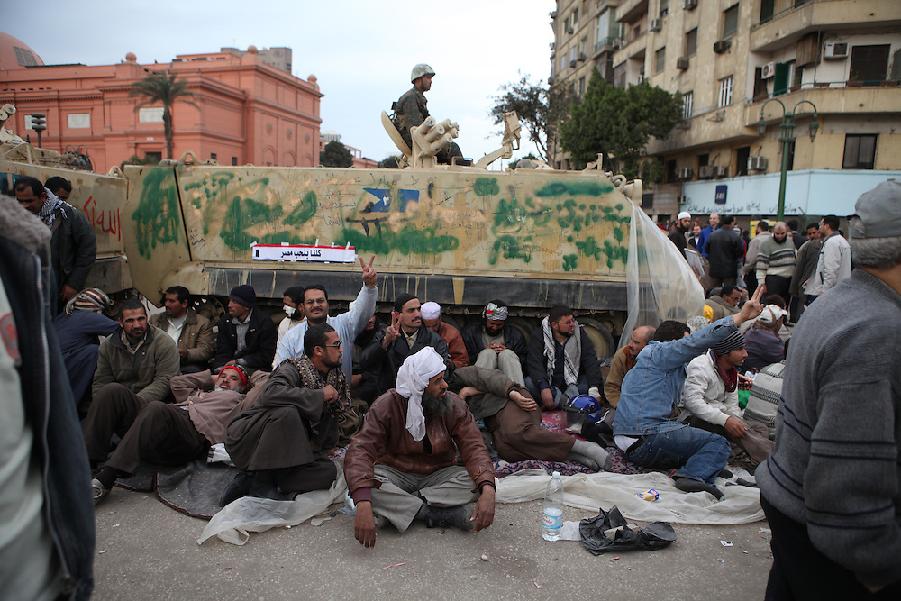 "On ""Sunday of the martyrs"" at Tahrir Square, Egyptian pro-democracy protesters sit in front of an army tank to prevent it from leaving or further entering the square."