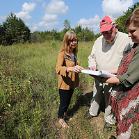 Mallie Fitzgerald, left, Edwina Carpenter, right, shows Hoyle Palmer the plans for the 80 acres of land he donated to the Brices Crossroads.
