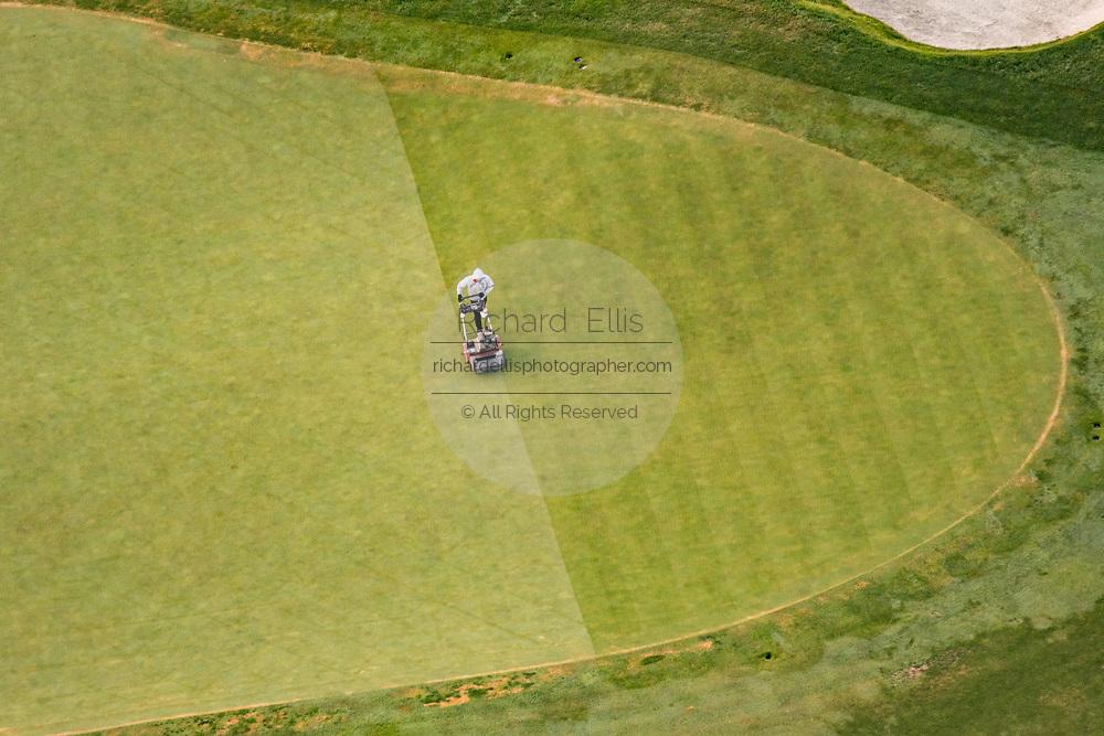 A landscaper mows a putting green at the Ventanas de San Miguel golf course outside the colonial city of San Miguel de Allende, Mexico.