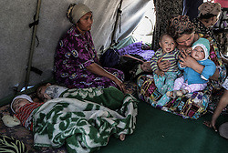 Ethnic Uzbeks, who left their destroyed houses, sit in a tent in a refugee camp at the border with Uzbekistan, some seven kilometres from the city of Osh, Kyrgyzstan, on 18 June 2010. Although there were no new reports of fighting on 18 June the refugee situation sparked by the recent violence continued, with tens of thousands of members of the Uzbek minority trying to flee into Uzbekistan while other ethnic Uzbeks trusting the currently calm situation decided to return to their homes in Kyrgyzstan.