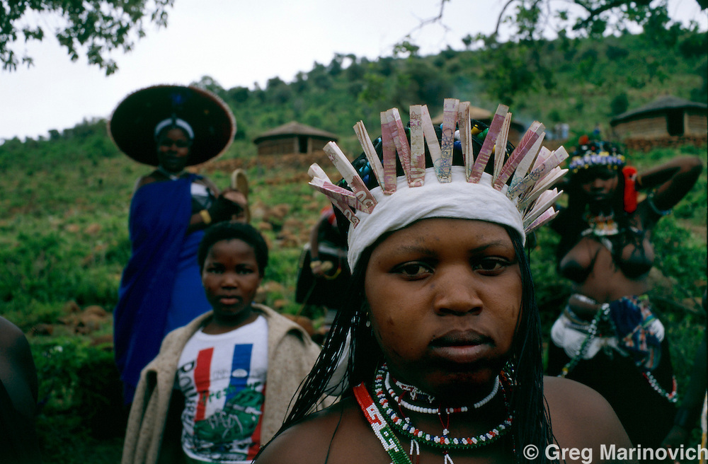 Msinga, KwaZulu Natal 10 September 1995. Girls who are undergoing a rite of passage to adulthood known as Memulo gather at Keate's Drift in the Msinga area of KwaZulu Natal region of South Africa. At rear is a mother, distinguished by her attire appropriate to a married woman.