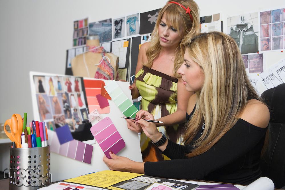Female fashion designers working at desk
