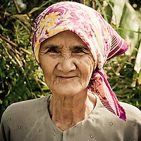 An elderly Vietnamese woman smiles at the Fairy Springs, Mui Ne, Vietnam, Southeast Asia.