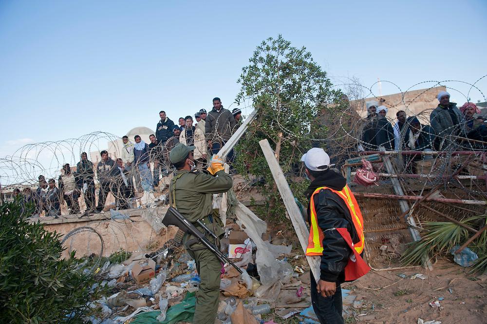 Un militaire accompagné par un bénévole Tunisien tente de protéger l'accès sur le territoire Tunisien en renforçant les barbelés installés. Poste Frontière de Ras Jedir, les réfugiés sont des milliers du coté Libyen de la frontière. Les militaires Tunisiens et les bénévoles sont obligés de fermer la frontière afin de pouvoir organiser leur accueil dans de bonnes conditions. Plus de 140 000 réfugiés ont déjà quitté la Libye par la Tunisie ou l'Egypte et des milliers continuent d'arriver chaque jours. Mardi 1er Mars 2011, poste frontière de Ras Jedir, Tunisie..© Benjamin Girette / AP